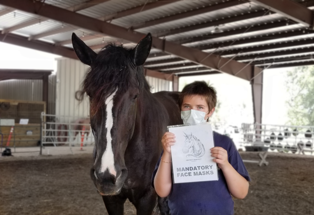 HHR Student holding sign stating face mask required.