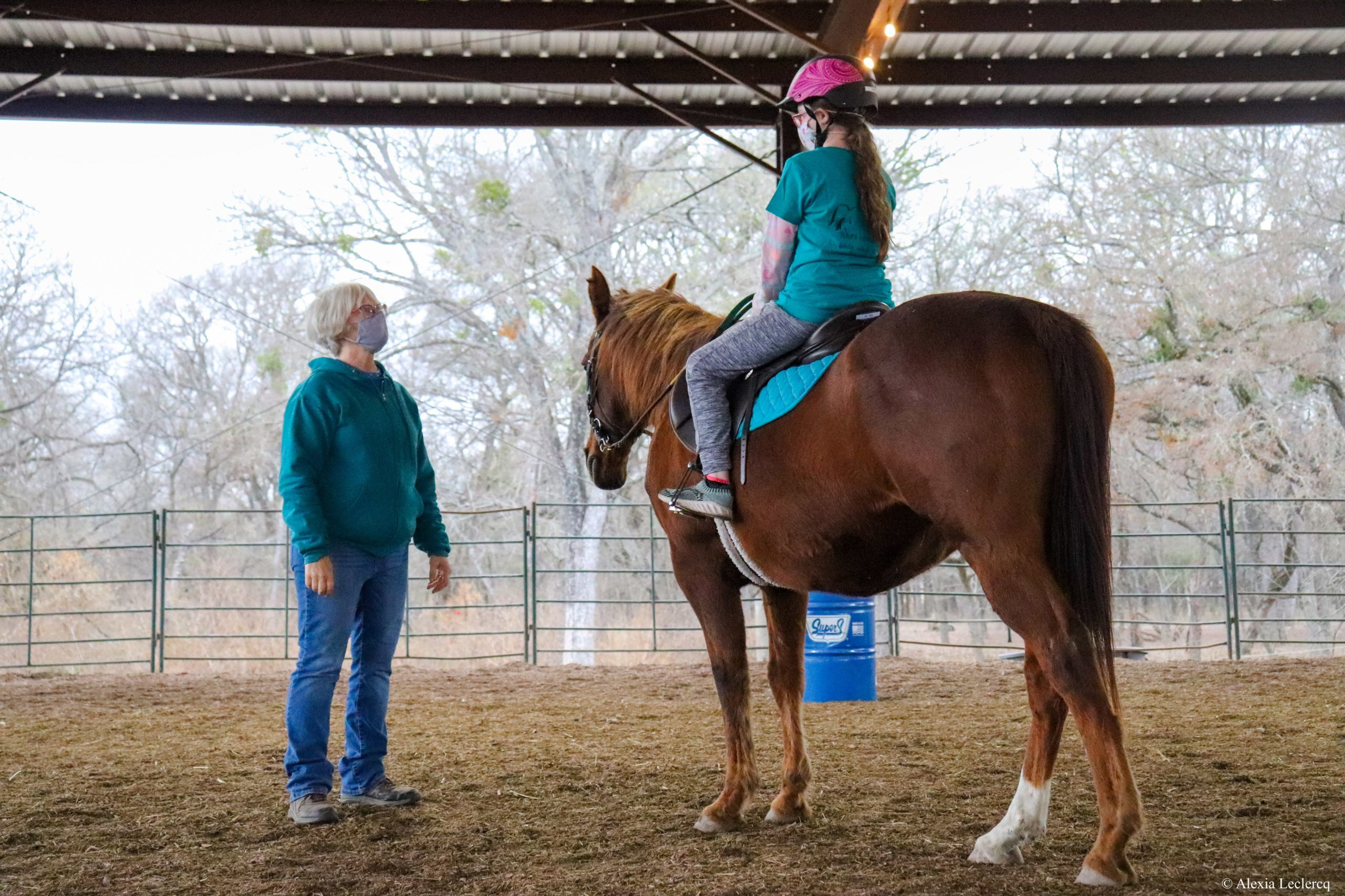 Instructor looking up at student on horseback.